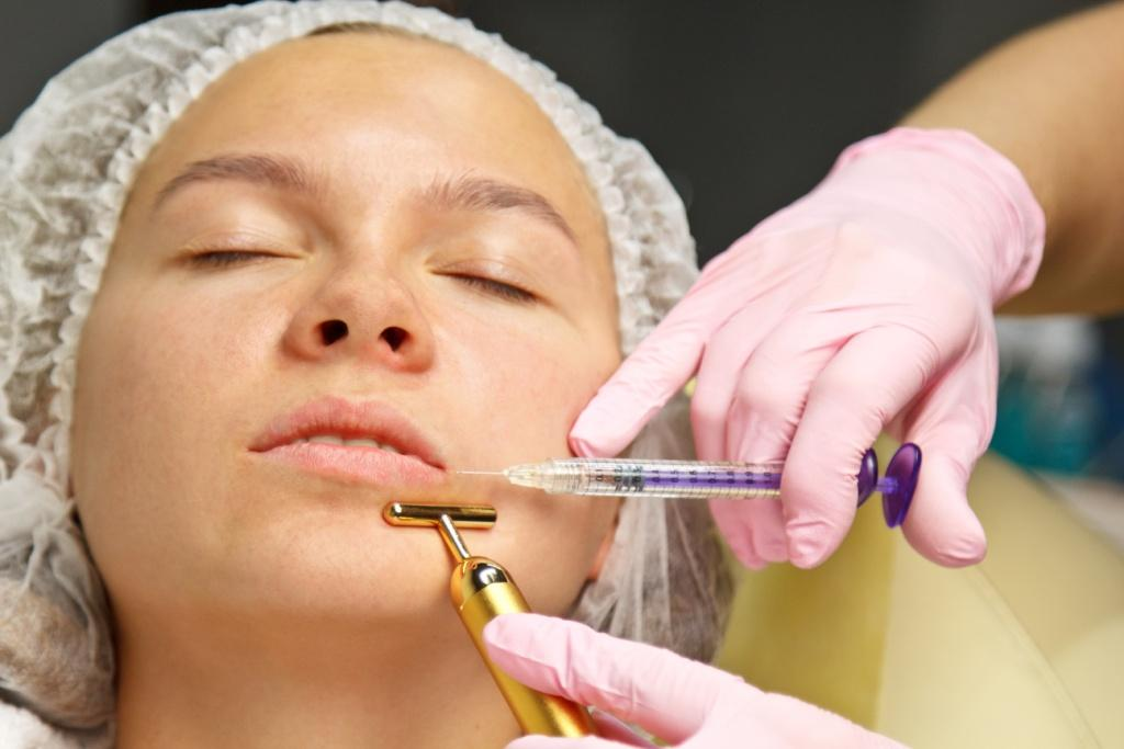 A cosmetologist injects a botulinum toxin to tighten and smooth out wrinkles on the skin of a female face.